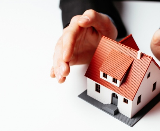 Home insurance concept. Man holding hands above miniature home